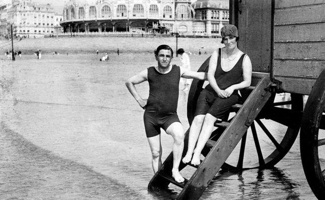 Jeune couple en voyage de noces au bord de la mer en 1923 à Deauville, devant une cabine de bain amovible. Le maillot «collant», longtemps décrié, est alors à la mode. © PFY